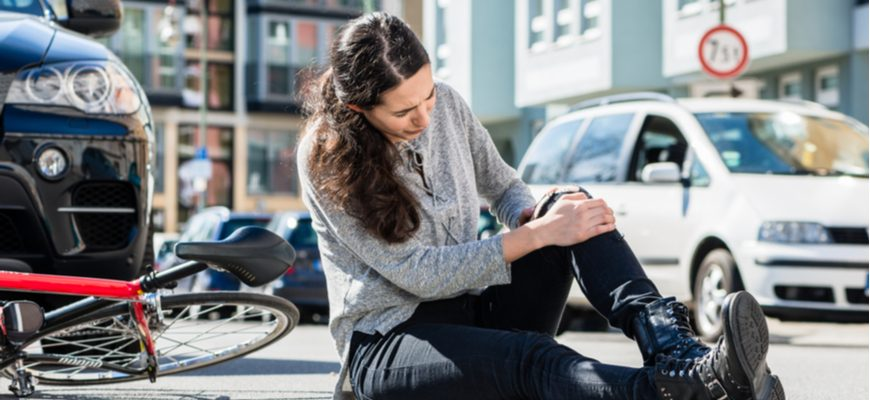car accident pain and suffering woman holding her knee sitting by car accident